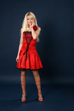 Blonde in a red satiny dress Royalty Free Stock Photography