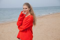 The blonde in the red walks along the beach of the sea coast. The blonde in the Red Sweater walks along the beach of the sea coast Royalty Free Stock Photos