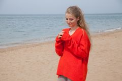 The blonde in the red walks along the beach of the sea coast. The blonde in the Red Sweater walks along the beach of the sea coast Royalty Free Stock Photo