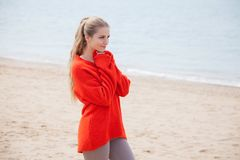 The blonde in the red walks along the beach of the sea coast. The blonde in the Red Sweater walks along the beach of the sea coast Stock Photography