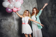 Blonde and redhead. Two young charming girlfriends at the party with balloons. On gray textured background Royalty Free Stock Photo