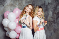 Blonde and redhead. Two young charming girlfriends at the party with balloons. On gray textured background Royalty Free Stock Photos