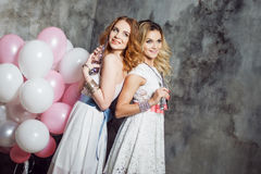 Blonde and redhead. Two young charming girlfriends at the party with balloons. On gray textured background Royalty Free Stock Image