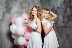 Blonde and redhead. Two young charming girlfriends at the party with balloons. On gray textured background Stock Photos