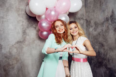 Blonde and redhead. Two young charming girlfriends at the party. Stock Photo