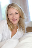Blonde reife Frau in der weißen entspannenden Kleidung Stockfotos