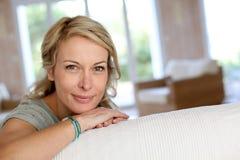 Blonde reife Frau, die auf dem Sofalächeln sich lehnt Lizenzfreie Stockbilder