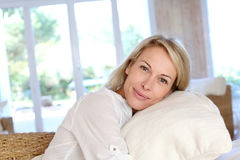 Blonde reife Frau, die auf Sofa liegt Stockfotos
