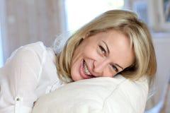 Blonde reife Frau, die auf Sofa sich lehnt Lizenzfreie Stockfotografie