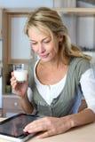 Blonde reife Frau, die ein Glas Milch trinkt Lizenzfreie Stockfotos