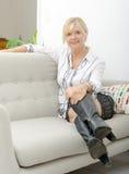 Blonde reife Frau, die im Sofa sich entspannt Lizenzfreies Stockfoto