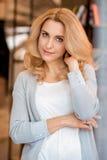Blonde reife Frau, die Kamera lächelt und betrachtet Lizenzfreie Stockfotos
