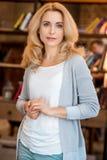 Blonde reife Frau, die Kamera lächelt und betrachtet Lizenzfreies Stockfoto