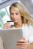 Blonde reife Frau, die Kreditkarte und den Einkauf verwendet Lizenzfreies Stockfoto