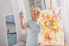Blonde reife Frau, die selfie nimmt Stockbild