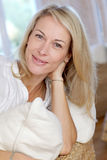 Blonde reife Frau, die sich zu Hause entspannt Lizenzfreie Stockfotos