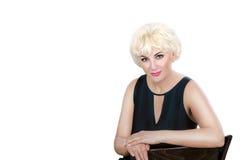Blonde reife Frau im schwarzen Cocktailkleid, das auf weißem Hintergrund aufwirft Stockbilder