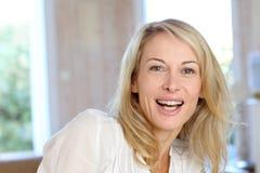 Blonde reife Frau zu Hause Stockfotografie