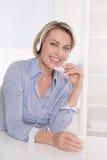 Blonde reife Geschäftsfrau mit Kopfhörer am Schreibtisch im Büro. Stockfotos