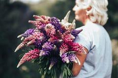 Blonde reife Stoutfrau, die einen lupine Blumenstrauß auf Naturhintergrund hält Der Schönheitsbegriff und das Körper-Positiv Klar stockfoto
