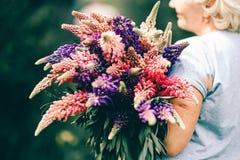 Blonde reife Stoutfrau, die einen lupine Blumenstrauß auf Naturhintergrund hält Der Schönheitsbegriff und das Körper-Positiv Klar stockfotos