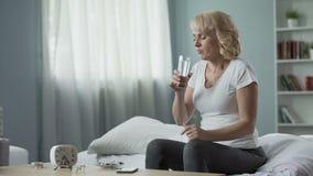 Blonde rijpe vrouwelijke zitting op bed en het nemen van pillen, gezondheid en geneeskunde stock footage