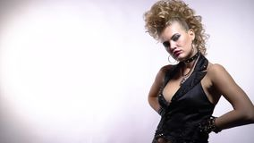 Blonde rocker woman wearing spiked vest and black gloves, white background. Young hot woman in black rocker clothes with metal spikes, with makeup and crazy stock video