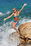 Blonde on rocky beach Stock Image