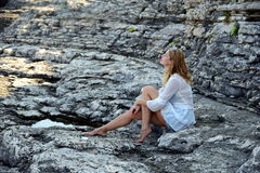 Blonde on rocky beach. Pula, Croatia stock photos