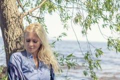 Blonde romantische Frau im Park nahe Fluss Stockfoto