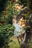 Blonde romantische leichte stilvolle schöne kaukasische Braut, die auf Baum sitzt Lizenzfreies Stockbild