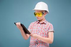 Blonde rubio del adolescente en el casco de la construcción con un destornillador y un martillo Fotos de archivo libres de regalías