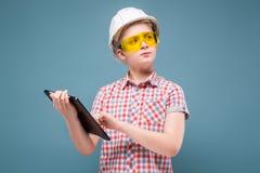 Blonde rubio del adolescente en el casco de la construcción con un destornillador y un martillo Fotografía de archivo libre de regalías