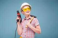 Blonde rubio del adolescente en el casco de la construcción con un destornillador y un martillo Imágenes de archivo libres de regalías