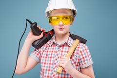 Blonde rubio del adolescente en el casco de la construcción con un destornillador y un martillo Fotos de archivo