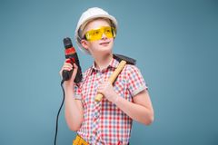 Blonde rubio del adolescente en el casco de la construcción con un destornillador y un martillo Foto de archivo libre de regalías