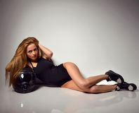 Blonde russian woman lying on the floor with black motorcycle he Royalty Free Stock Photography