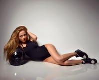 Blonde russische Frau, die auf dem Boden mit schwarzem Motorrad er liegt Lizenzfreie Stockfotografie