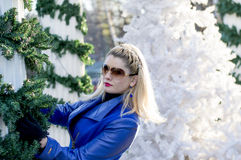 The blonde`s portrait in a blue coat at New Year`s scenery Royalty Free Stock Images