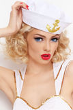 Blonde sailor. Young beautiful girl with blond curly hair and stylish make-up dressed as sailor royalty free stock photos