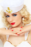 Blonde sailor. Young beautiful girl with blond curly hair and stylish make-up dressed as sailor stock photo