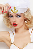 Blonde sailor. Young beautiful girl with blond curly hair and stylish make-up dressed as sailor royalty free stock images