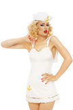 Blonde sailor. Young beautiful slim girl with blond curly hair and stylish make-up dressed as sailor, over white background royalty free stock photos