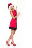 Blonde Santa Girl, die auf weiße Wand zeigt Stockfoto