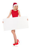 Blonde Santa Girl, die weißes Plakat hält Stockbild