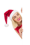 Blonde Santa Girl hinter einem Plakat Stockfoto