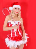 Blonde Santa girl with huge candy cane stick on red Royalty Free Stock Image