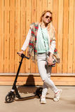 Blonde in scarf with scooter Royalty Free Stock Images