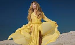 Blonde schöne Dame im gelben Kleid Stockfotos