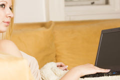 Blonde schöne Frau mit Laptop auf dem Bett Stockbild